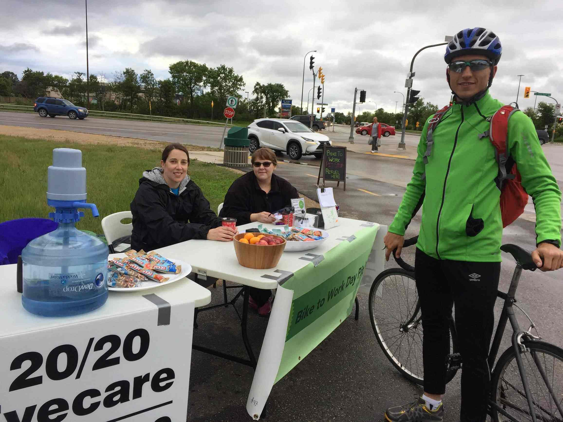 20/20 Staff posing with cyclist at pit stop table